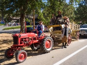 Old tractor and wagon with costumed parade participants