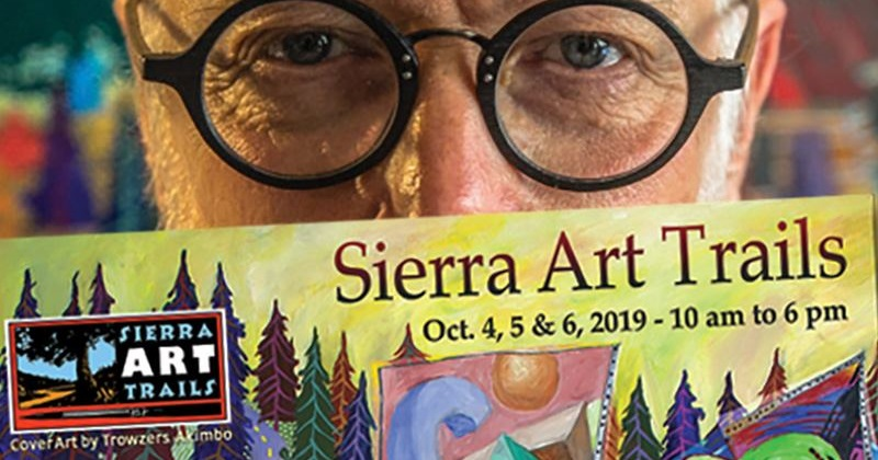 Artist Trowzers Akimbo, wearing glasses, peers over Sierra Art Trails cover he created