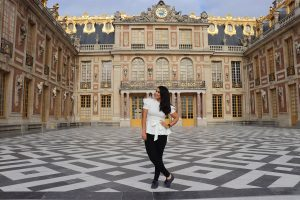 Brunette woman posing in front of Versailles Castle