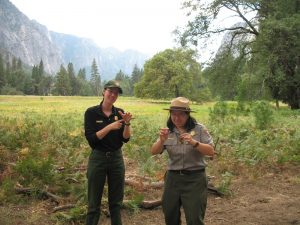 A uniformed park ranger provides American Sign Language interpretation in Yosemite National Park