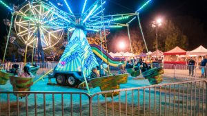 Nighttime image of lighted carnival midway ride with children and Ferris wheel