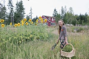 Becca Zollinger stands in a field of sunflowers