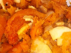 Extreme close-up fills the frame with roasted butternut squash and apple slices cooking together