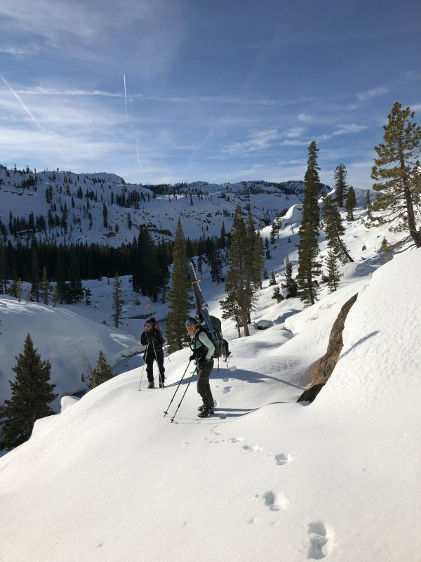 Ski-clad snow surveyors stand on snowy bank in Yosemite under blue skies