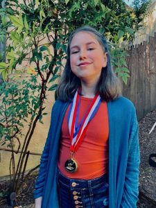 Shows a female teenager wearing two gold medals she won in the academic pentathlon.