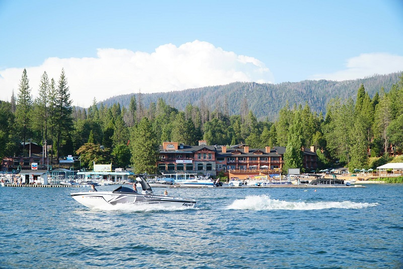 Shows a wide shot of the resort from the lake with a speedboat passing by
